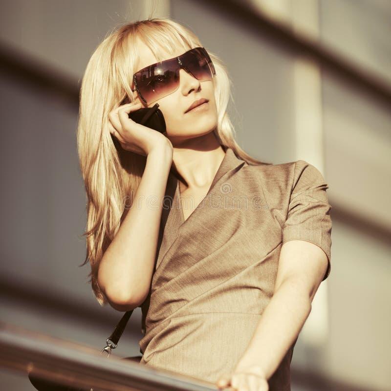Jonge manier bedrijfsvrouw die in zonnebril celtelefoon uitnodigt stock foto