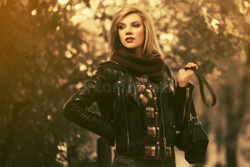 Jonge manier blonde vrouw die in zwart leerjasje in stadspark lopen royalty-vrije stock fotografie