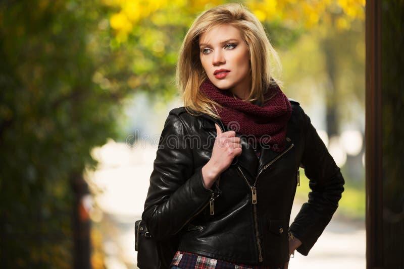 Jonge manier blonde vrouw in leerjasje in de herfstpark royalty-vrije stock fotografie
