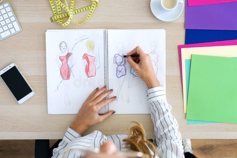 Jonge manierontwerper die een paar schetsen in het naaien van workshop trekken royalty-vrije stock afbeeldingen