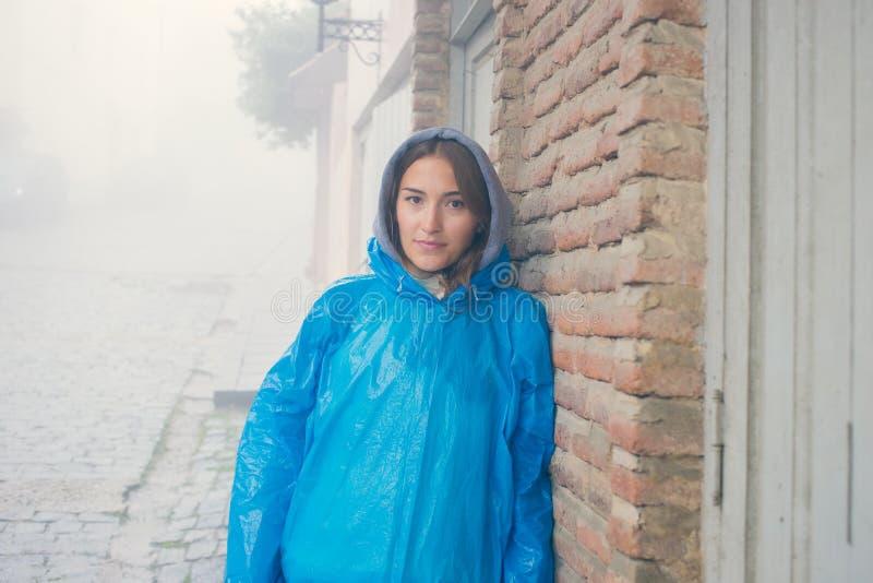 Jonge maniervrouw in blauwe regenjas die in mist zich in openlucht bevinden bakstenen muur van het oude huis Betonmolens Een motr stock afbeelding