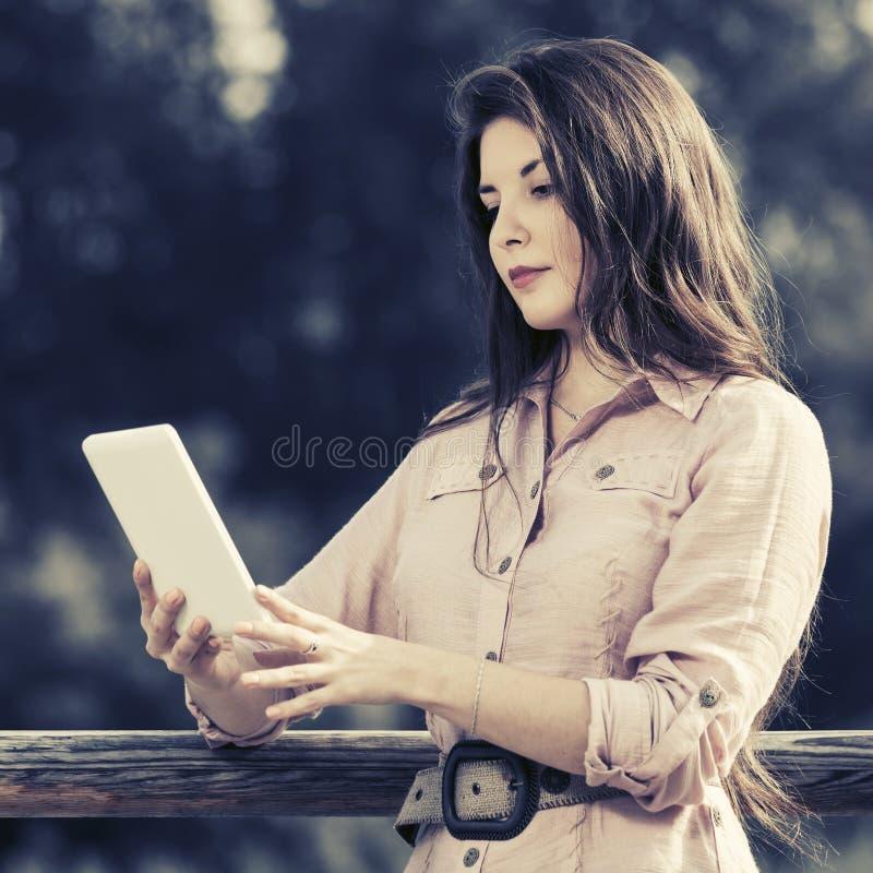Jonge maniervrouw die digitale tabletcomputer met behulp van openlucht stock foto's