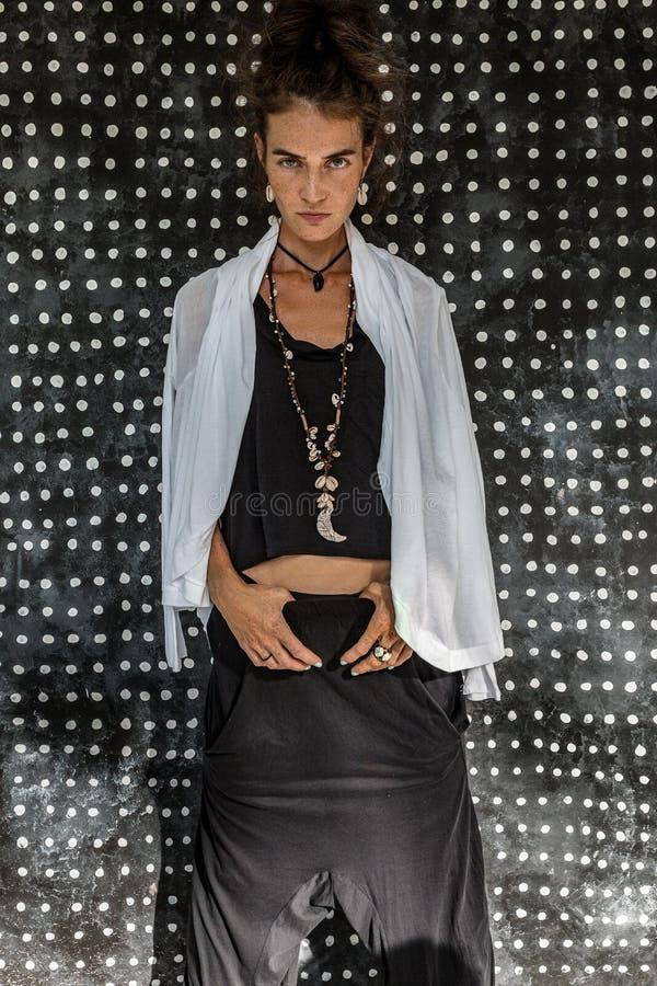 Jonge maniervrouw in het zwarte kleding stellen op eenvoudige achtergrond stock afbeeldingen