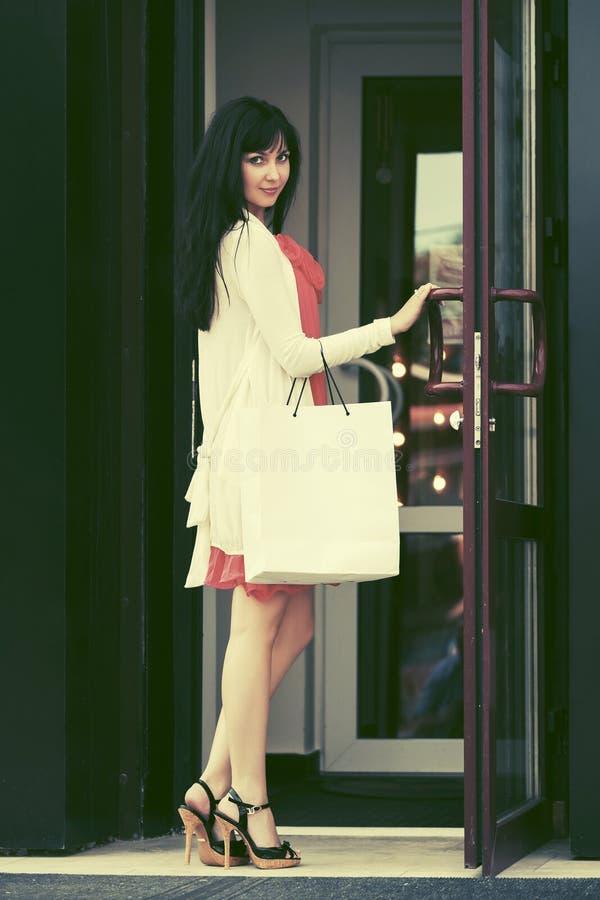 Jonge maniervrouw met het winkelen zakken bij de wandelgalerijdeuropening royalty-vrije stock fotografie
