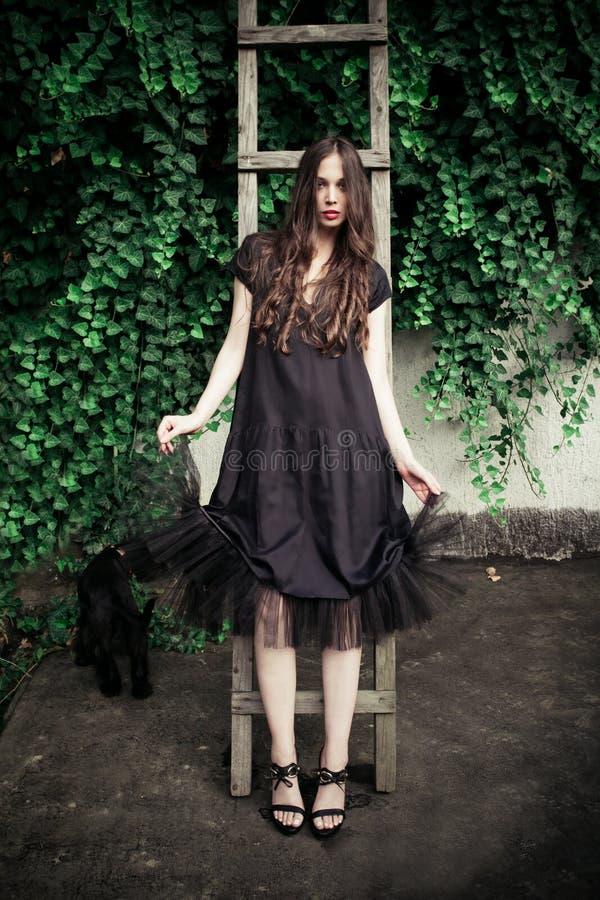 Jonge maniervrouw in zwarte elegante kledingshelling op houten ladder royalty-vrije stock afbeelding