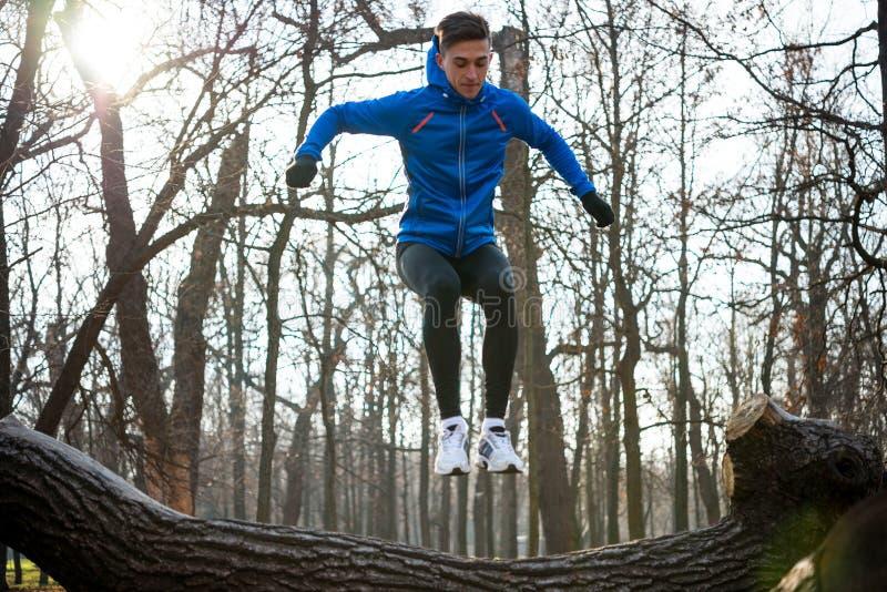 Jonge Mannelijke Agent die op Login het Park in Koud Sunny Autumn Morning springen Gezond levensstijl en sportconcept stock foto's