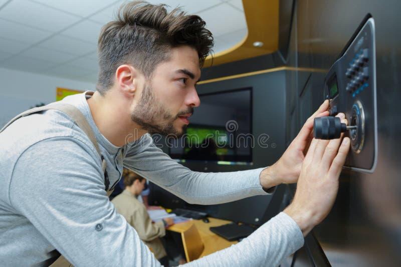 Jonge mannelijke arbeider die elektronisch toetsenbord met behulp van stock afbeelding