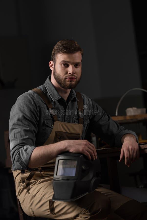jonge mannelijke arbeider in eenvormig holdings beschermend masker stock afbeelding