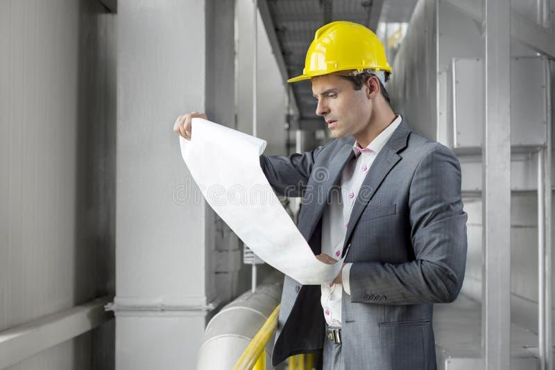 Jonge mannelijke architect die blauwdruk in de industrie onderzoeken royalty-vrije stock afbeelding