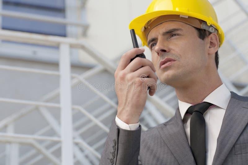 Jonge mannelijke architect die op bidirectionele radio tegen de bouw spreken stock foto