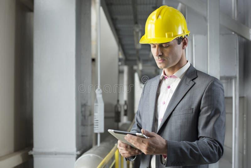 Jonge mannelijke architect die tabletcomputer in de industrie met behulp van stock afbeeldingen