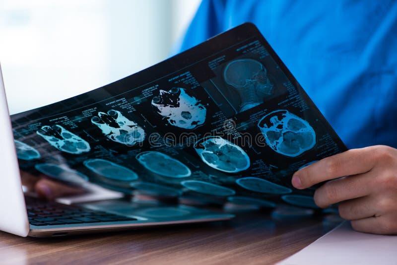 Jonge mannelijke arts die x-ray beelden bekijken stock foto's