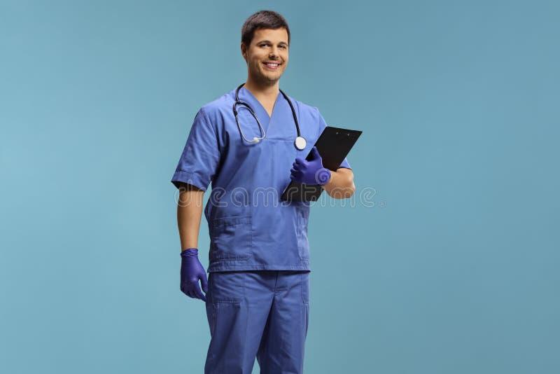Jonge mannelijke arts in eenvormige dragende handschoenen en het houden van een klembord royalty-vrije stock fotografie