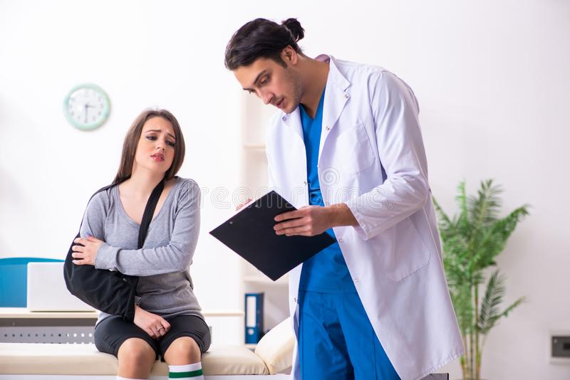 Jonge mannelijke arts en vrouwelijke mooie patiënt stock foto's