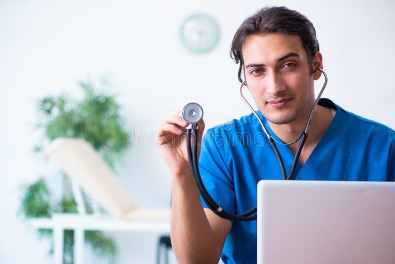 Jonge mannelijke arts met stethoscoop stock afbeeldingen