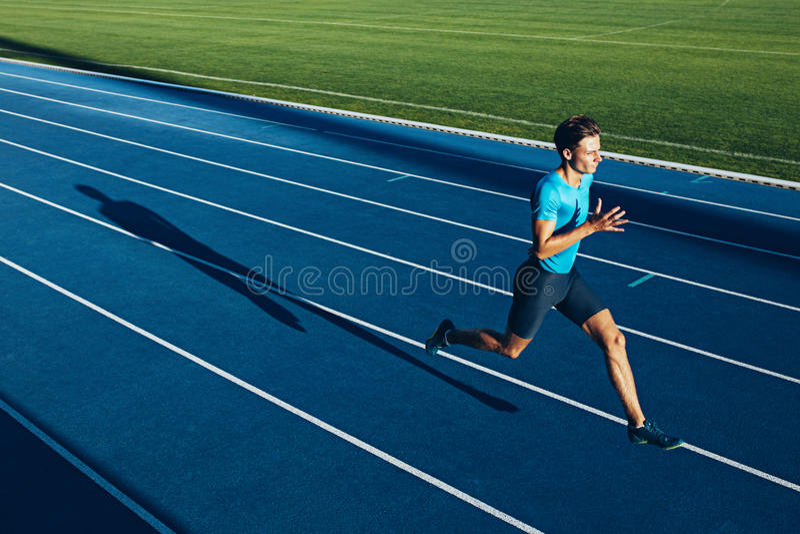 Jonge mannelijke atleet opleiding op een rasspoor royalty-vrije stock afbeeldingen