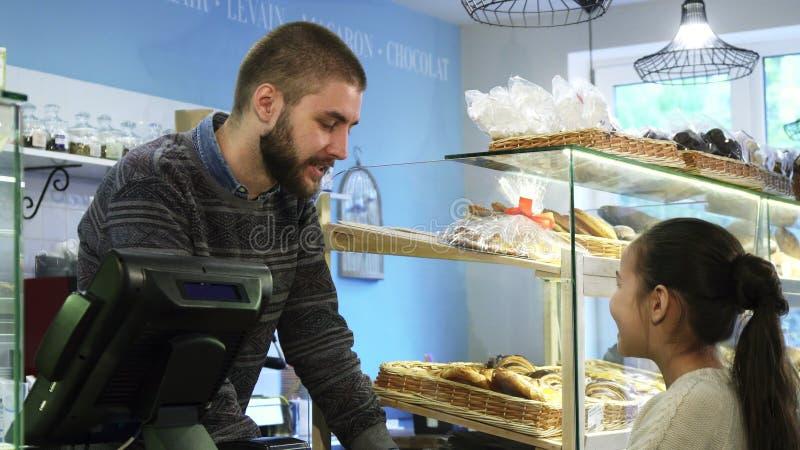 Jonge mannelijke bakker die bij zijn opslag werken die meisje helpen die desserts kiezen stock afbeeldingen