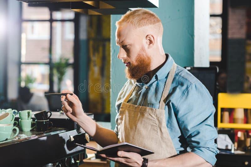 jonge mannelijke barista die zich in koffiewinkel bevinden royalty-vrije stock afbeelding