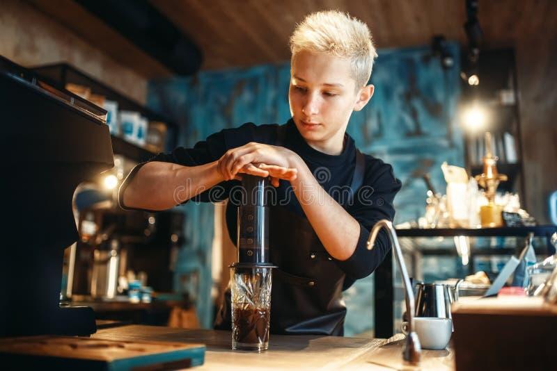 Jonge mannelijke barista maakt verse espresso in koffie royalty-vrije stock foto's