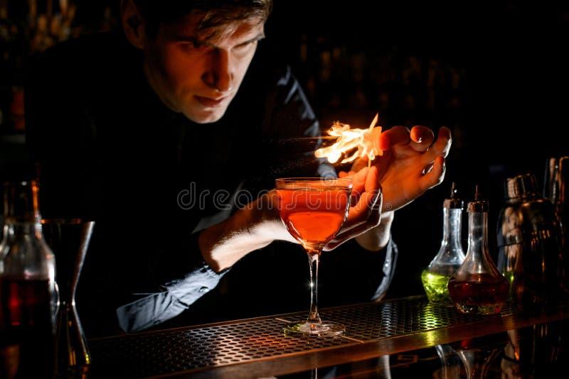 Jonge mannelijke barkeeper sprinkhaan naar alcoholische cocktail met een stuk citruszest en vuren royalty-vrije stock afbeelding