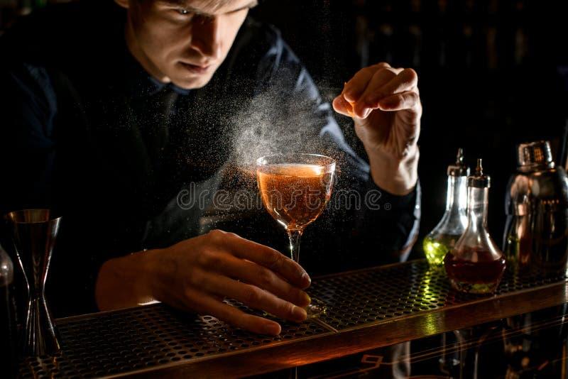 Jonge mannelijke barkeeper sprinkhaan tot alcoholische cocktail met een stuk citruszest stock foto
