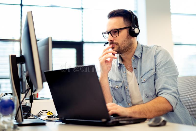 Jonge mannelijke call centreexploitant die aan zijn computer werken terwijl hallo royalty-vrije stock foto