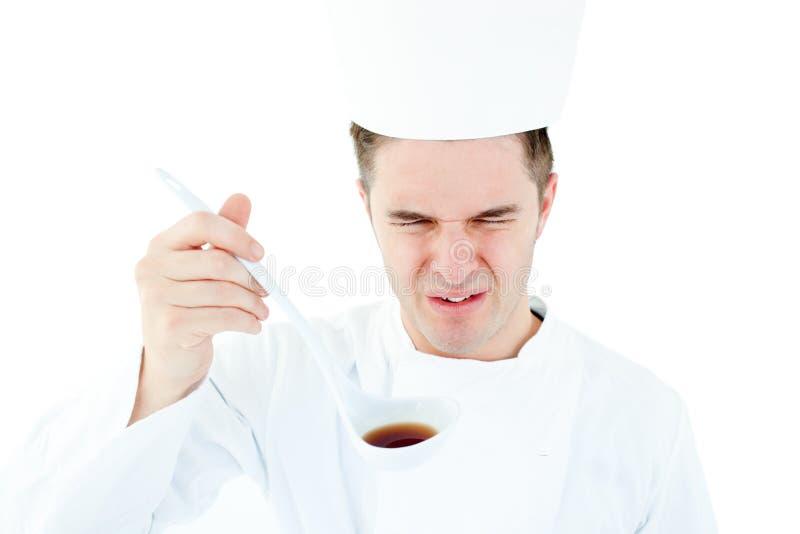 Jonge mannelijke chef-kok die een soep met vervormd gezicht proeft stock afbeeldingen