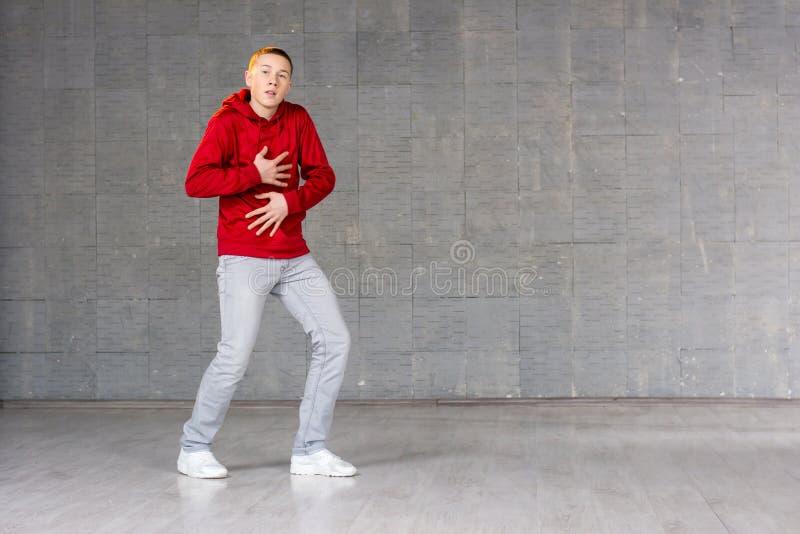 Jonge mannelijke danser op grijze achtergrond stock afbeeldingen