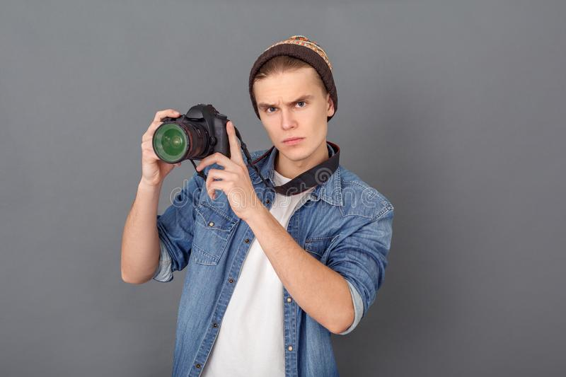 Jonge mannelijke die fotograaf in de studio van het jeansjasje op grijze holdingscamera omhoog wordt geïsoleerd royalty-vrije stock fotografie