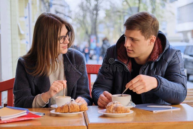 Jonge mannelijke en vrouwelijke vriendenstudenten die in openluchtkoffie, het spreken die, het drinken koffie, thee zitten, crois stock foto