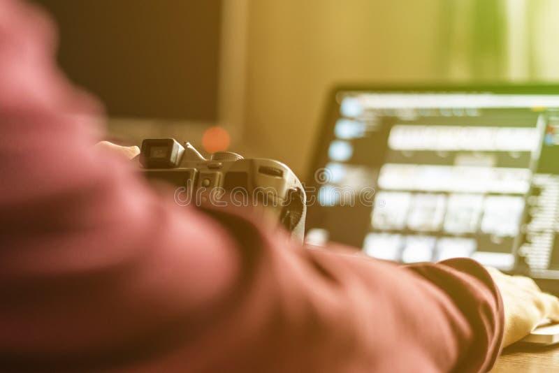 Jonge mannelijke fotograaf die een camera houden en zijn foto's op laptop in de studio F prcessing stock fotografie