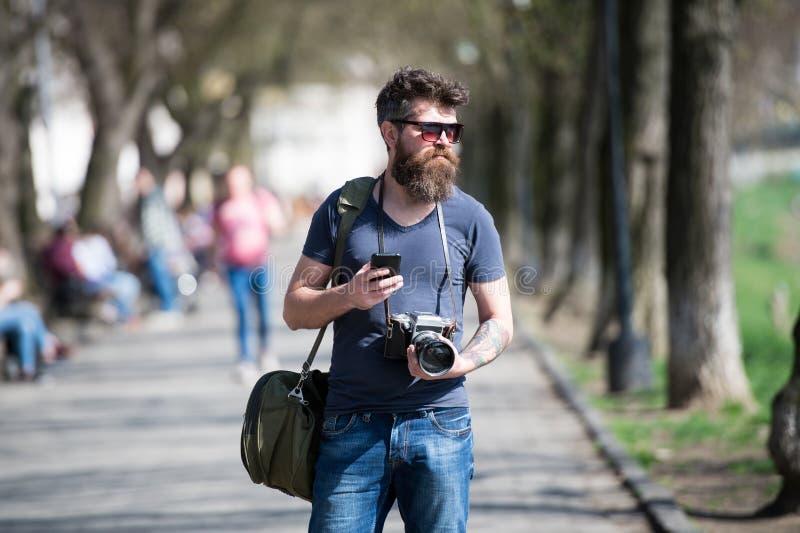 Jonge mannelijke fotograafwandeling rond stad in onderzoek naar perfect beeld Gebaarde mens in modieuze eyewear holdingswijnoogst royalty-vrije stock fotografie