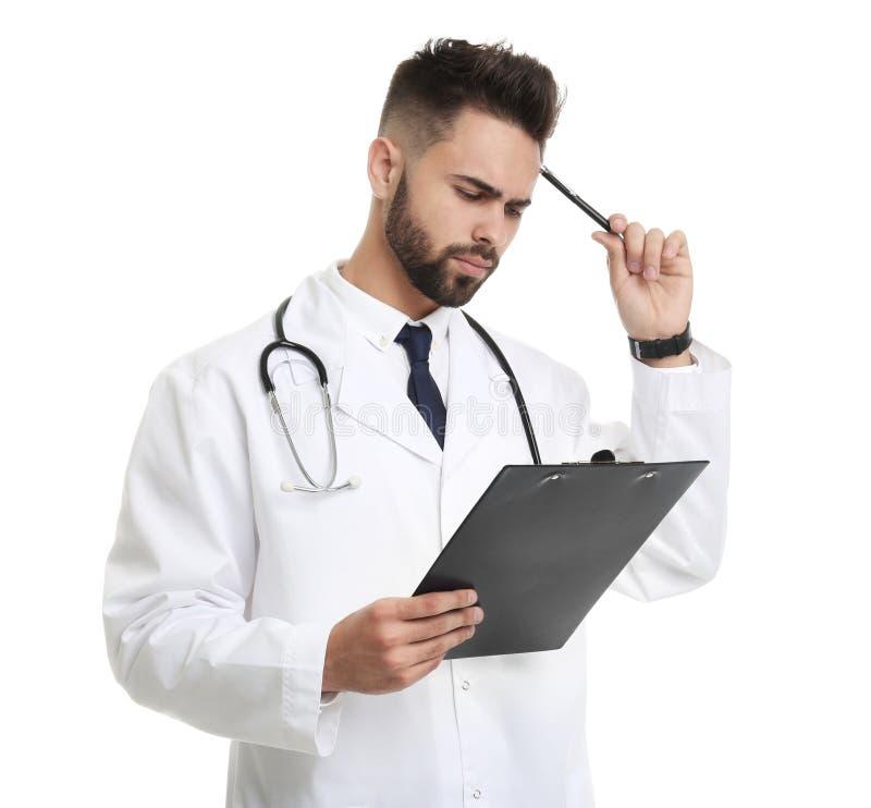 Jonge mannelijke geïsoleerde arts in eenvormig met klembord stock foto