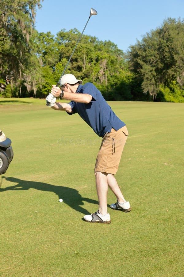 Jonge Mannelijke Golfspeler die de Golfbal voorbereidingen treft te raken royalty-vrije stock fotografie