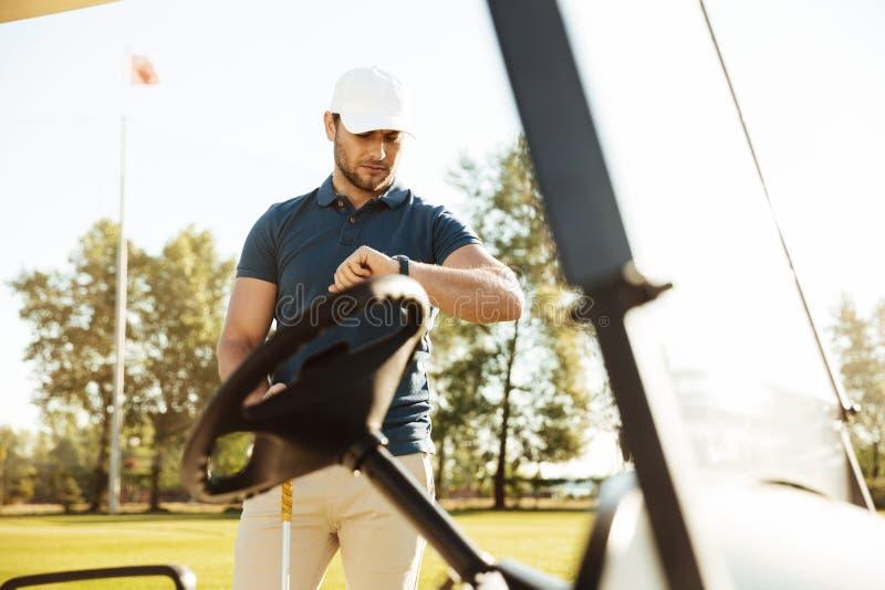Jonge mannelijke golfspeler die een polshorloge bekijken stock afbeelding