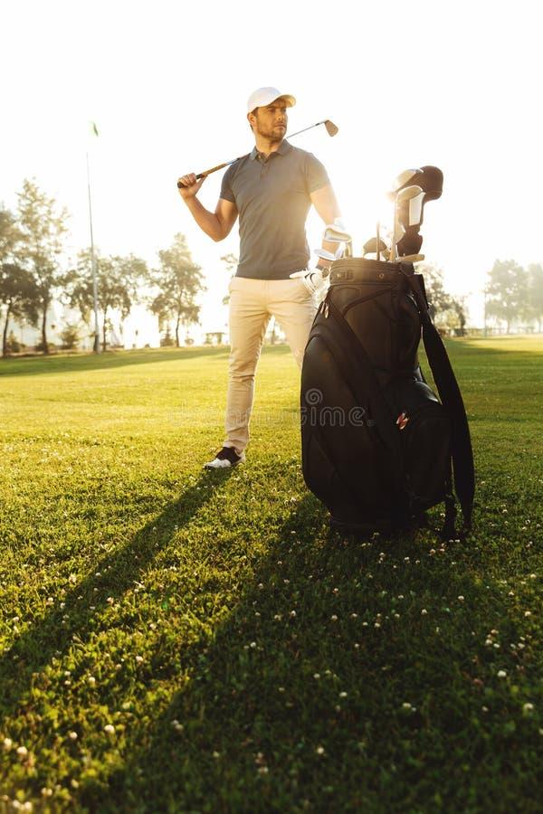 Jonge mannelijke golfspeler die zich op een groen gebied bevinden royalty-vrije stock fotografie