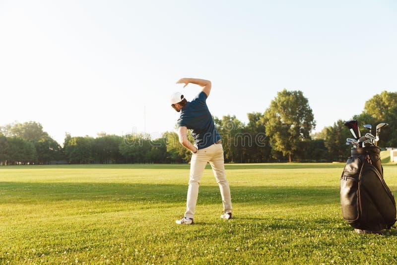 Jonge mannelijke golfspeler het uitrekken zich spieren alvorens het spel te beginnen stock afbeeldingen