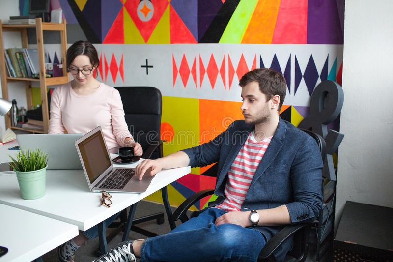 Jonge mannelijke het bespreken zaken met vrouw in modern bureau royalty-vrije stock fotografie
