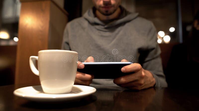 Jonge mannelijke het scrollen smartphone in koffie, surfend Internet, gadgetverslaving royalty-vrije stock afbeeldingen