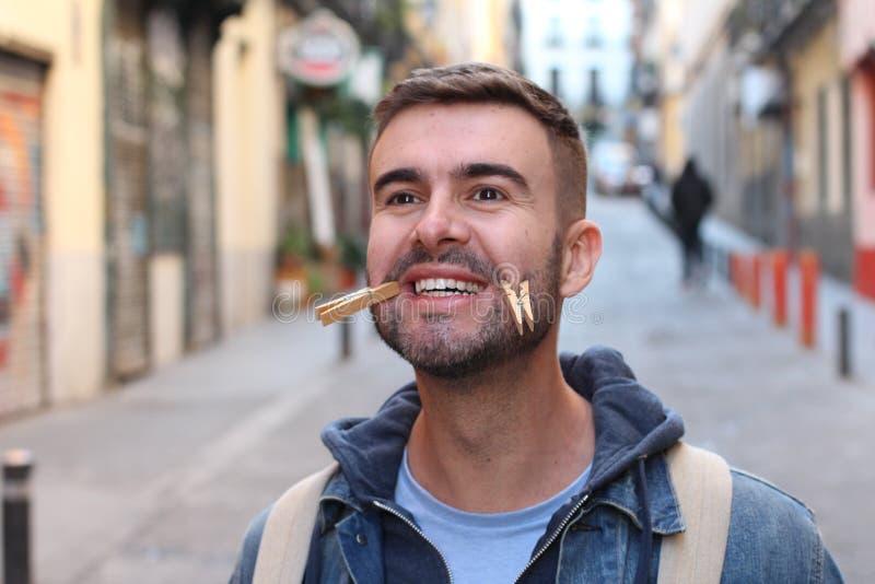 Jonge mannelijke het vervalsen glimlach met wasknijpers stock afbeeldingen