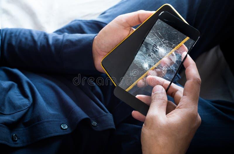 Jonge mannelijke holdingssmartphone en gebroken van het aangemaakte scherm van de glasfilm bescherming en gadget royalty-vrije stock foto's