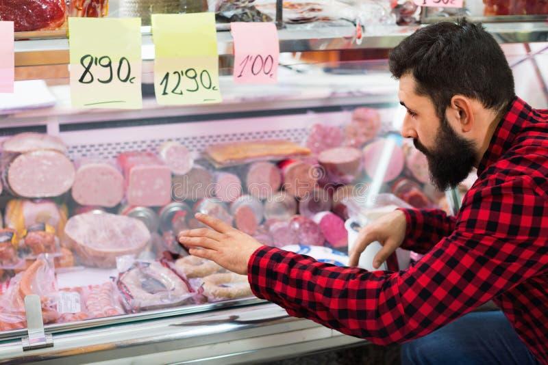 Jonge mannelijke klant die worsten in butcher'swinkel onderzoeken royalty-vrije stock afbeeldingen