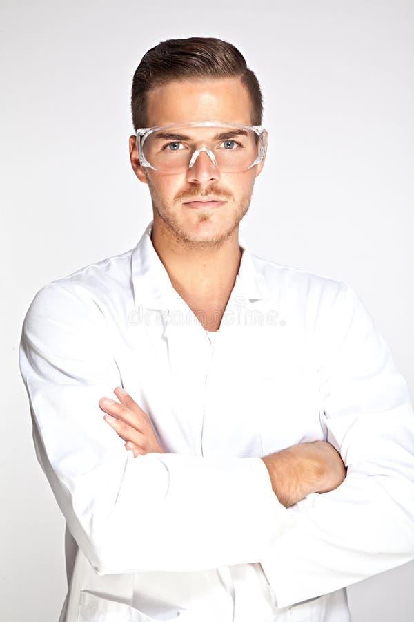 Jonge mannelijke laboratoriummedewerker met beschermende glazen stock fotografie