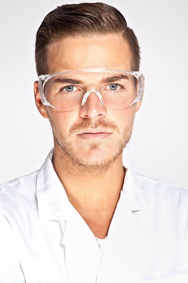 Jonge mannelijke laboratoriummedewerker met beschermende glazen royalty-vrije stock afbeeldingen