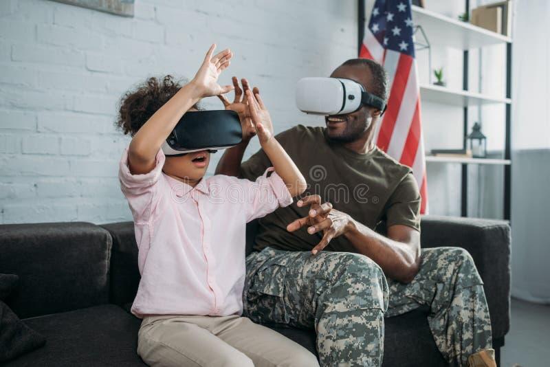 Jonge mannelijke militair in camouflagekleren en weinig dochter het gebruiken stock afbeeldingen