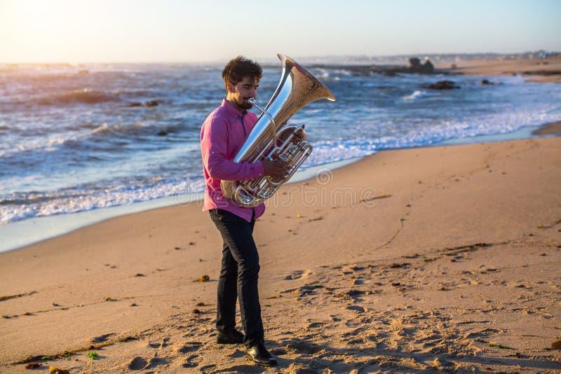 Jonge mannelijke musicus het spelen trompet op de kust royalty-vrije stock afbeelding