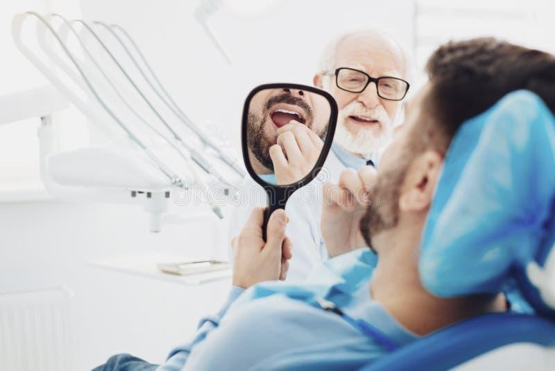 Jonge mannelijke patiënt betreffende zijn tanden royalty-vrije stock afbeeldingen