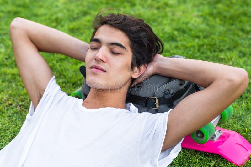 Jonge mannelijke schaatser die op het gras met zijn gesloten ogen rusten stock afbeeldingen