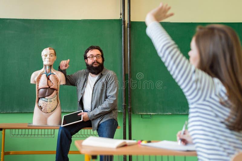 Jonge mannelijke Spaanse leraar in biologieklasse die, die digitale tablet houden en menselijk lichaamsanatomie onderwijzen, die  royalty-vrije stock foto
