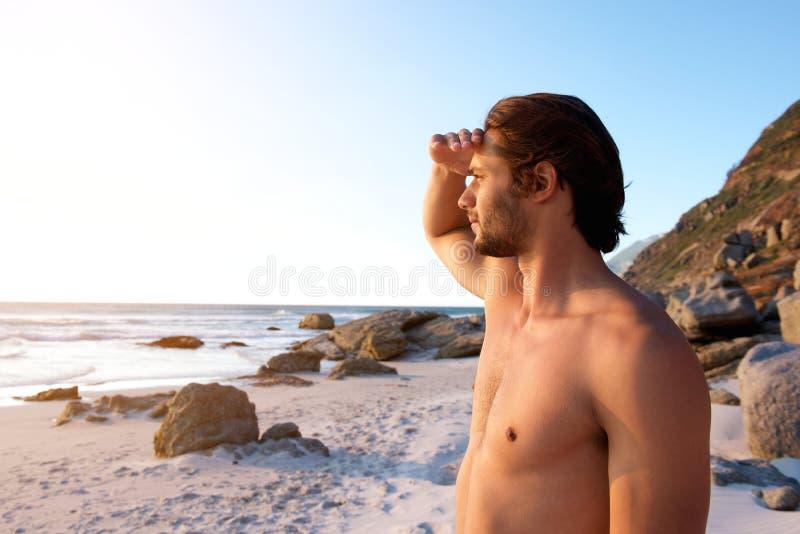 Jonge mannelijke status bij strand die water bekijken royalty-vrije stock foto